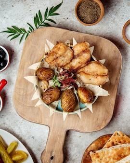Gebakken vis met gebakken aardappelen en uien