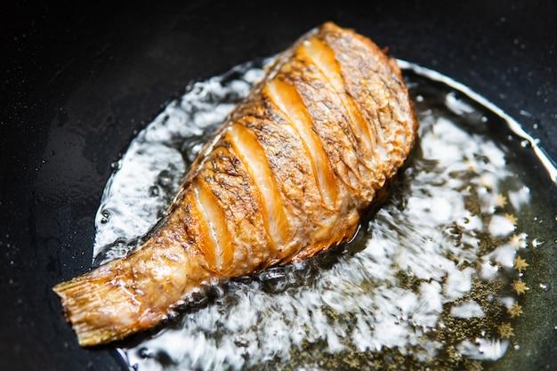Gebakken vis met kokende olie in de pan