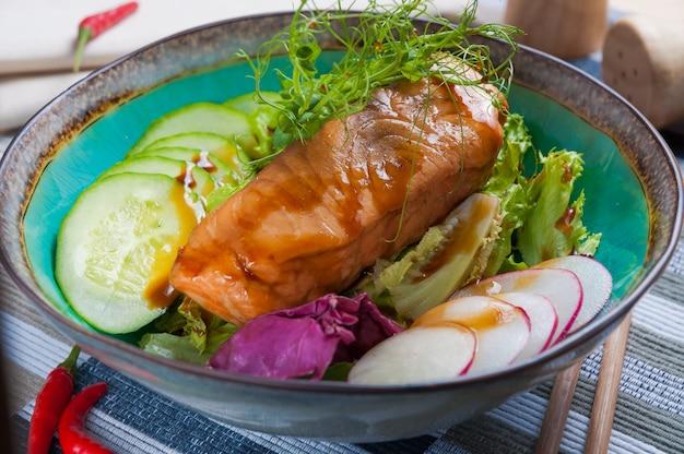 Gebakken vis met komkommers en radijsjes en kruiden. aziatische keuken