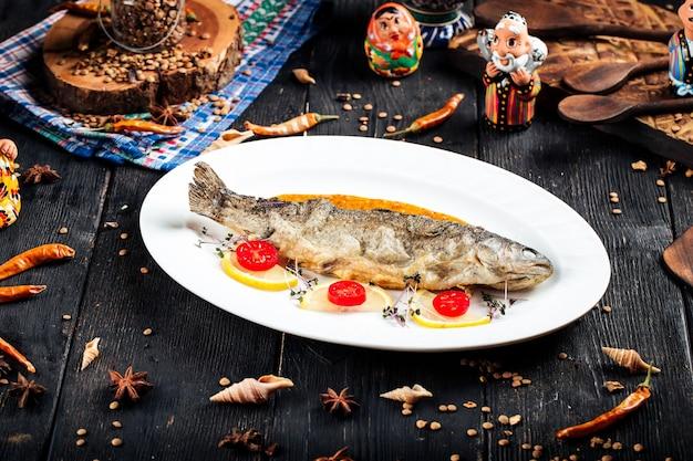 Gebakken vis met saus en citroen op de zwarte houten
