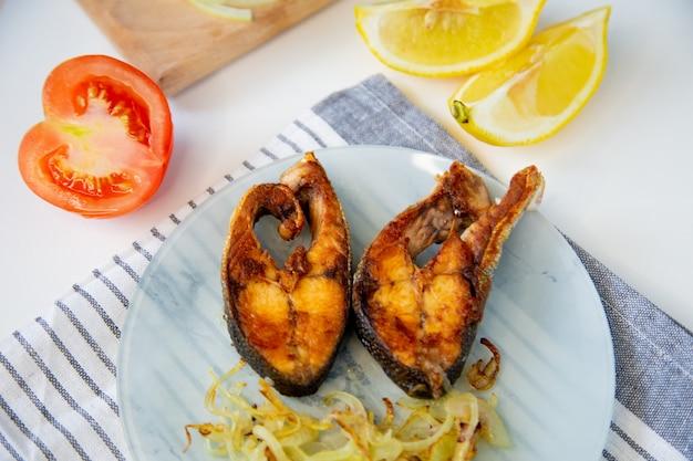 Gebakken vis met uien ligt op een bord op een wafeldoek ernaast is een snijplank met gehakt op...