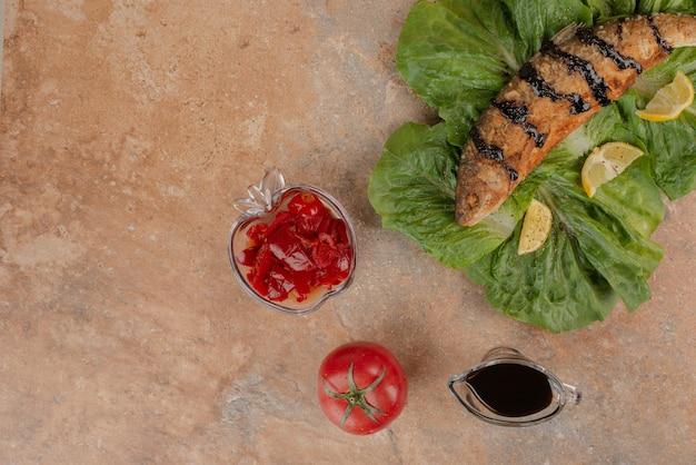 Gebakken vis op sla met schijfjes citroen, augurken en granaatappelsaus.