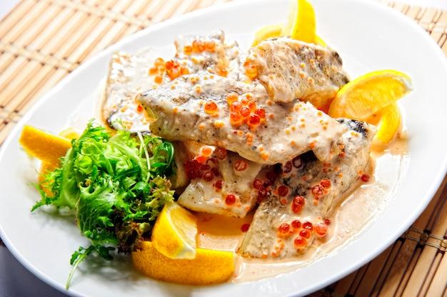 Gebakken visfilet met frietjes op witte plaat.