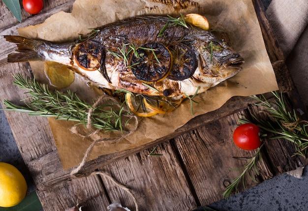 Gebakken vissendorado. gebakken doradovissen en ingrediënt voor het koken. zeebrasem dorade met zout, kruiden en peper