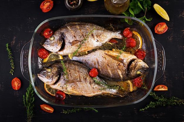 Gebakken vissendorado met citroen en kruiden in bakselpan op donkere rustieke achtergrond. bovenaanzicht gezond diner met visconcept. dieet en schoon eten