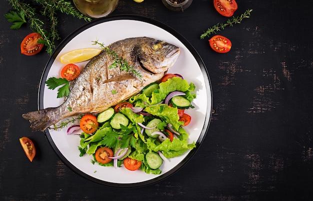 Gebakken vissendorado met citroen en verse salade in witte plaat op donkere rustieke achtergrond. bovenaanzicht gezond diner met visconcept. dieet en schoon eten