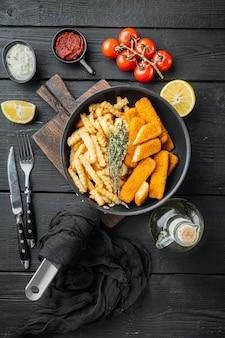 Gebakken visstick of frietjes vis met saus set, op frituurpan, op zwarte houten tafel achtergrond, bovenaanzicht plat lag