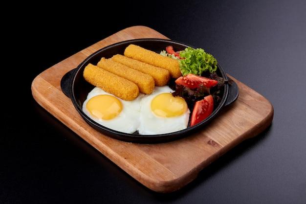 Gebakken vissticks in een gietijzeren pan. gebakken eieren, verse tomaten en salade.