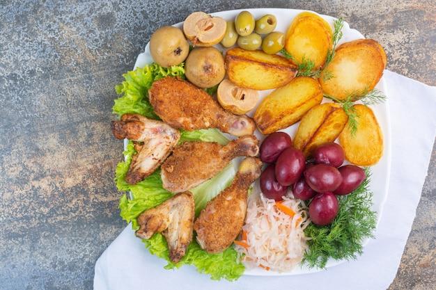 Gebakken vlees en aardappel naast ingeblikte groenten op een plaat op een doek.