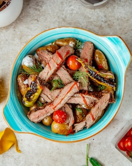 Gebakken vlees en aardappelen in de oven met tomaten en paprika bovenaanzicht