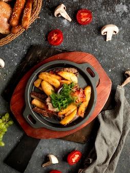Gebakken vlees en aardappelen in een aluminium koekepan
