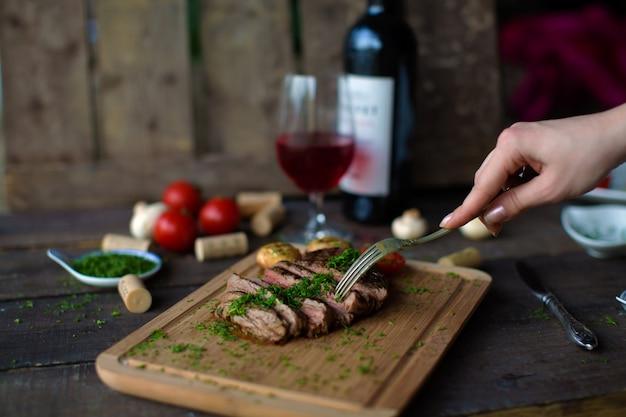 Gebakken vlees en aardappelen op een houten bord