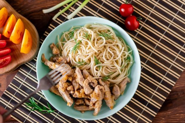 Gebakken vlees en spaghetti op een bord op een houten ondergrond met tomaten en kruiden.