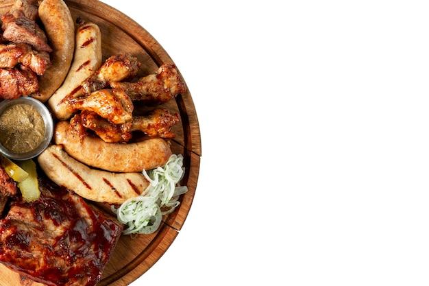 Gebakken vlees en worstjes met saus op een houten bord. diverse gegrilde hapjes. bovenaanzicht. geïsoleerd op een witte achtergrond. ruimte voor tekst.