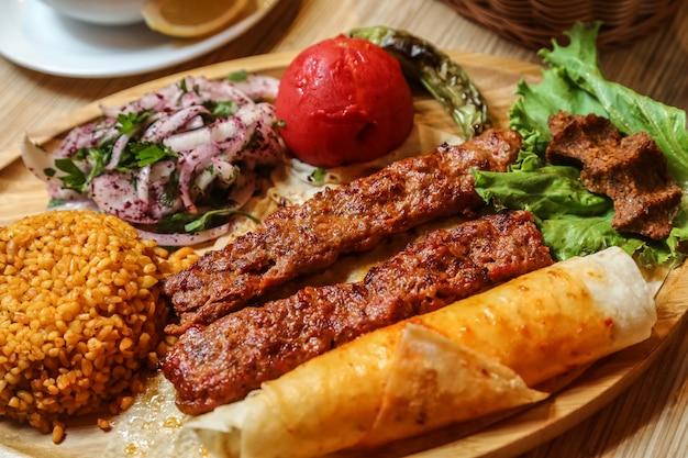 Gebakken vlees lula met gesneden ui met kruiden en brood