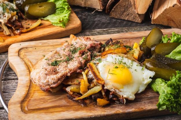 Gebakken vlees met gebakken aardappelen, eieren en gezouten komkommers op een houten bord.