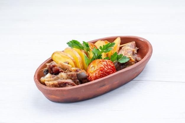 Gebakken vlees met greens en gebakken pruimen in bruine plaat op licht bureau, eten vleesgerecht diner