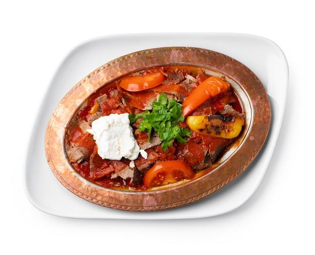 Gebakken vlees met groenten in tomatensaus op wit wordt geïsoleerd