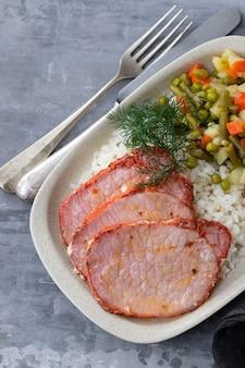 Gebakken vlees met groenten in witte schotel