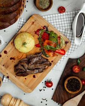 Gebakken vlees met groenten op houten bord