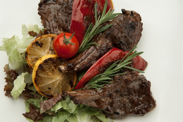 Gebakken vlees met tomaat en citroen op witte achtergrond close-up geroosterd vlees ribben