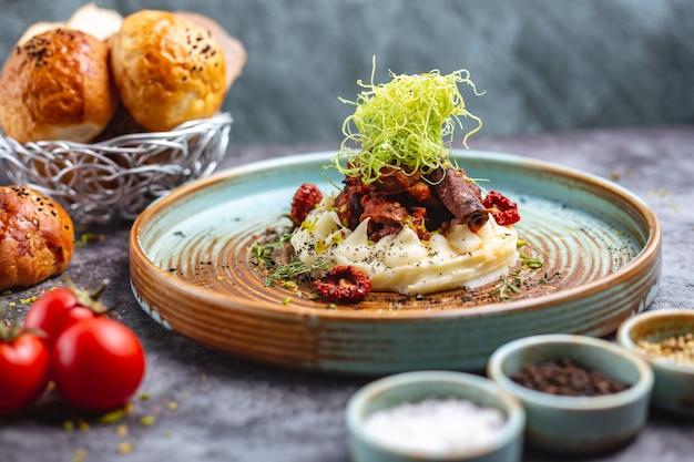 Gebakken vlees op aardappelpuree gegarneerd met geraspte paprika en tijm