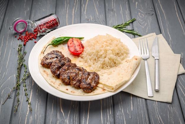 Gebakken vlees, witte rijst en groenten op houten tafel