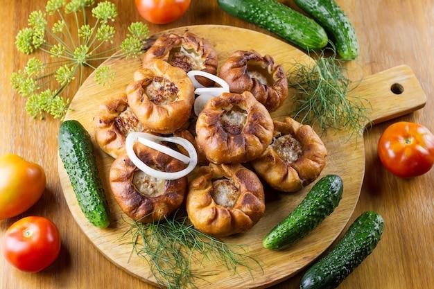 Gebakken vleespastei belyash met groenten op een houten bord, bovenaanzicht