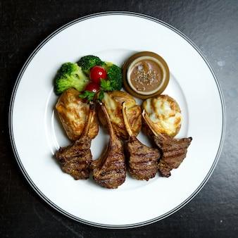 Gebakken vleesribben met groenten en aardappels