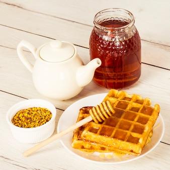 Gebakken wafel; honing; theepot en bijenpollen op houten tafel