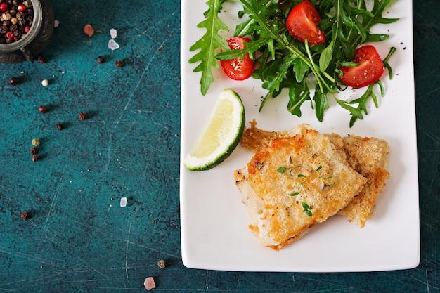 Gebakken witte visfilets en tomatensalade met rucola. bovenaanzicht