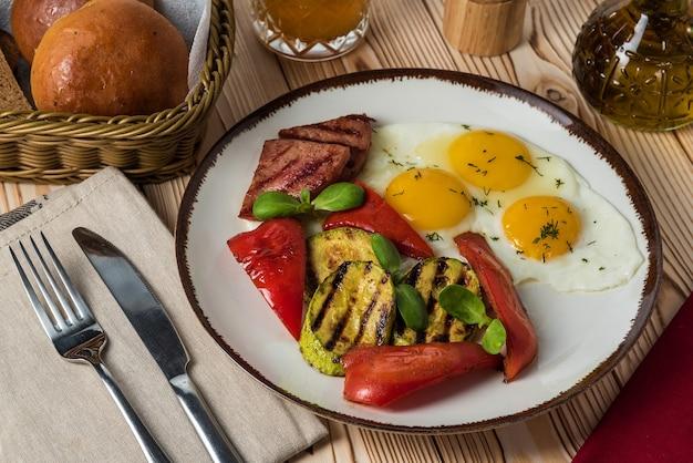 Gebakken worst met gebakken eieren en peper en courgette op een rustieke achtergrond