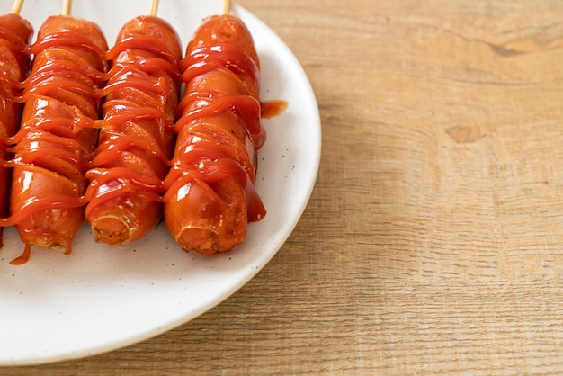 Gebakken worst spies met ketchup op witte plaat