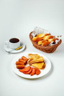 Gebakken worst worst en pannenkoek plaat zwarte thee en ontbijt voor het ontbijt