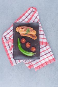 Gebakken worsten met groenten op een zwart bord.