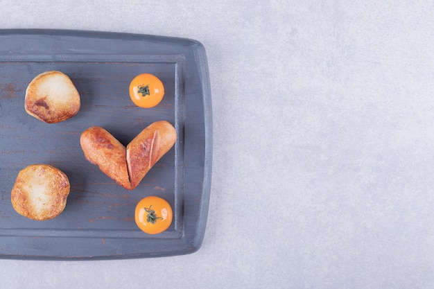 Gebakken worstjes en aardappelen op donker bord.