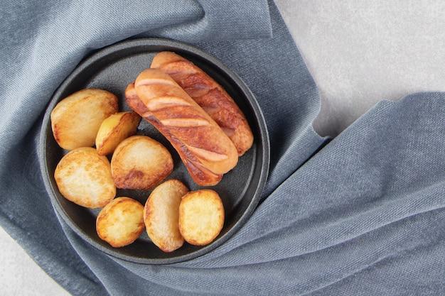 Gebakken worstjes en aardappelen op zwarte plaat.
