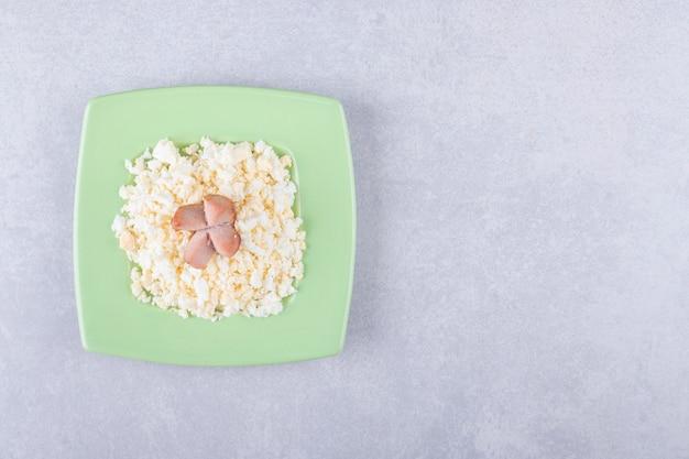 Gebakken worstjes en macaroni op groene plaat.