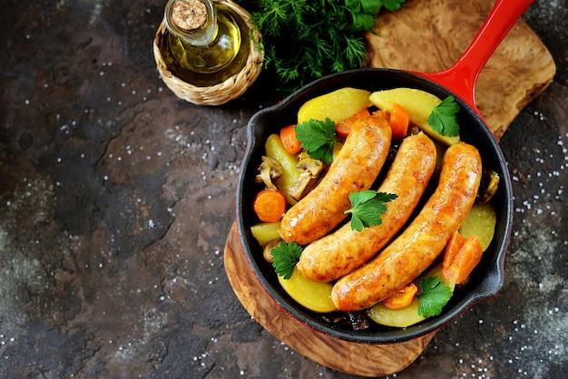 Gebakken worstjes met aardappelen, champignons en uien in een pan