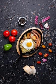 Gebakken worstjes met aardappelen en gebakken eieren geserveerd restaurant, op zwart met rode tomaten, brood, rode groene paprika en broccoli
