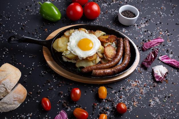 Gebakken worstjes met aardappelen en gebakken eieren, op zwart met rode tomaten, brood, rode groene paprika en broccoli