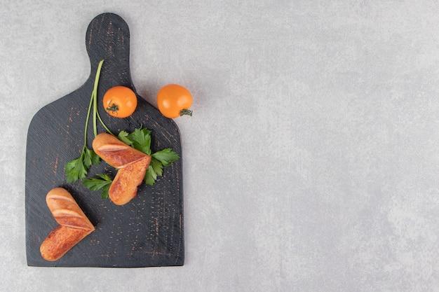 Gebakken worstjes met tomaten op zwart bord.