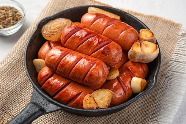 Gebakken worstjes met uien, knoflook en kruiden in een koekenpan op een grijze achtergrond