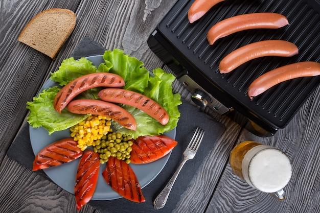 Gebakken worstjes op een plaat met groenten en gegrilde worstjes