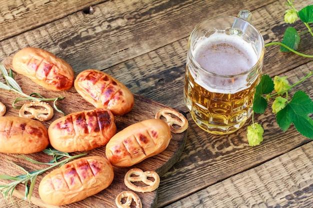 Gebakken worstjes op houten snijplank en glas bier met hopplant op houten bord. bbq, picknick