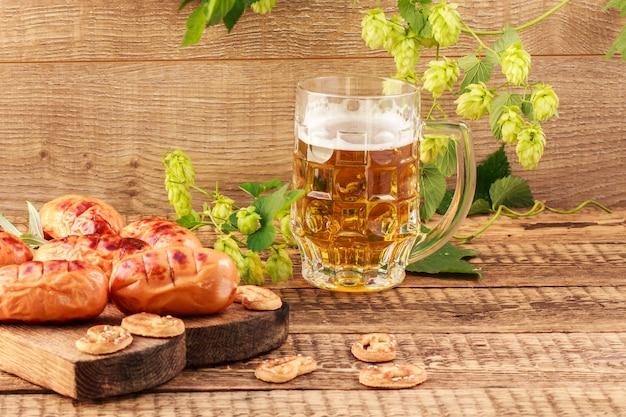 Gebakken worstjes op houten snijplank en glas bier op houten ondergrond met hopplant. bbq, picknick