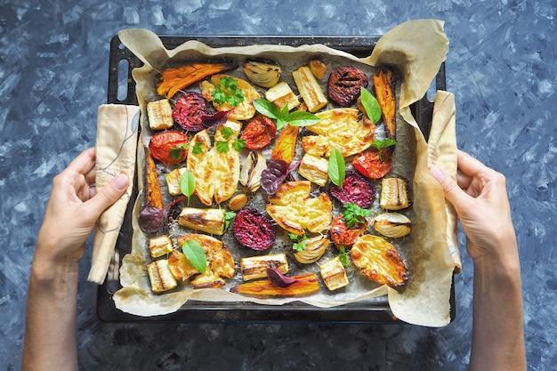 Gebakken wortelen, bieten, aardappelen, courgette en tomaten op een bakplaat, bovenaanzicht