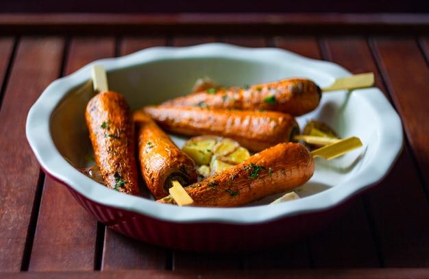 Gebakken wortelen in een ronde ovenschaal op houten achtergrond. vegetarisch voedselconcept