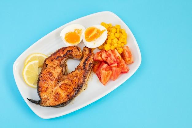 Gebakken zalm met gekookt ei, tomaat en maïs op witte schotel