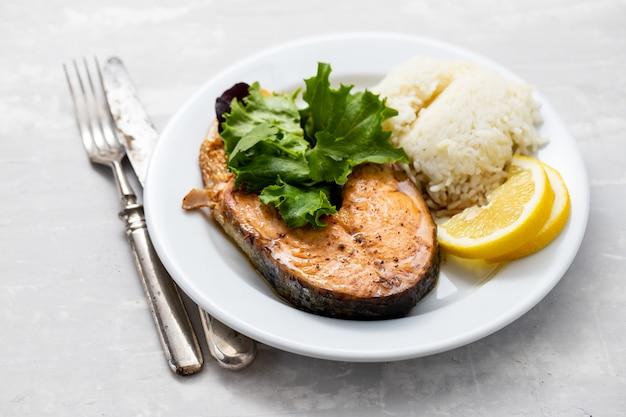 Gebakken zalm met gekookte rijst, salade en citroen op witte plaat